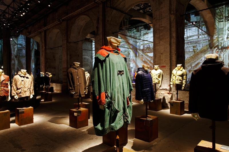 Various jackets on display, with green and red cape jacket in the center, on mannequin busts, arranged under brick archway
