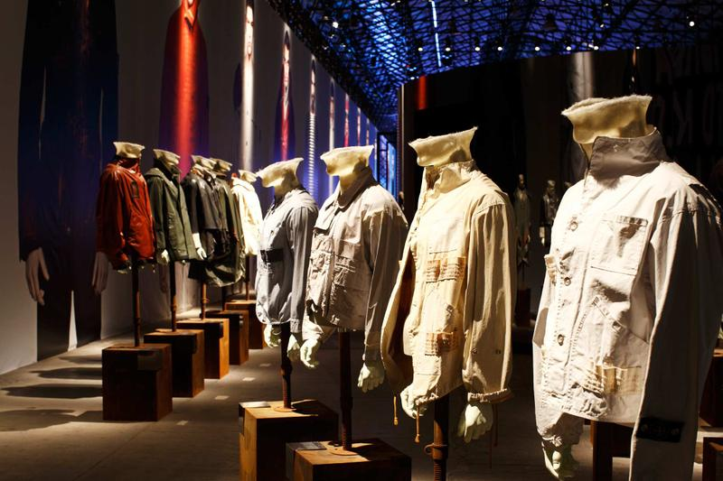 Line up of nine jackets in different styles and colors on mannequin busts in exhibition hall