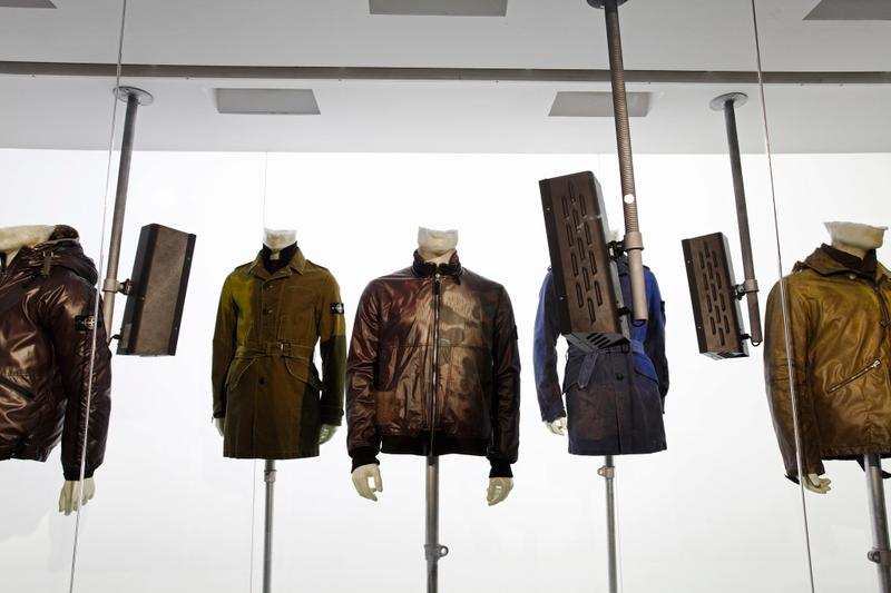 Various dark jackets on display on mannequin busts in front of white wall