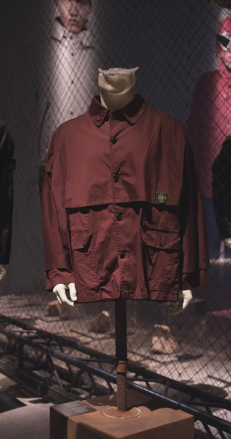 Dark red multi flap button down collared jacket with patch on the front displayed on mannequin bust with photos in the background