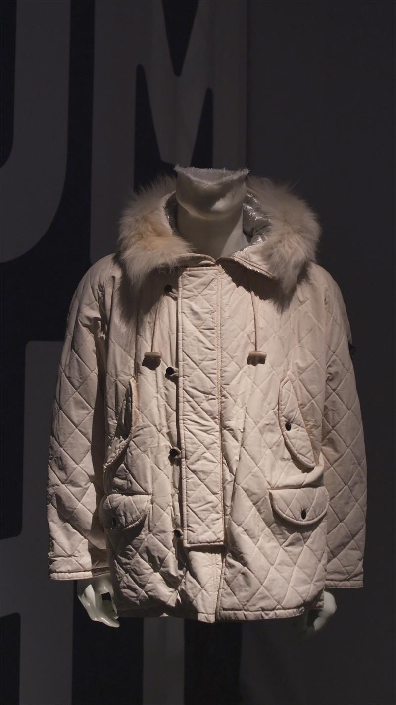 Off white quilted jacket with fur trimmed collar, toggle closure, and buttoned pockets displayed on mannequin bust