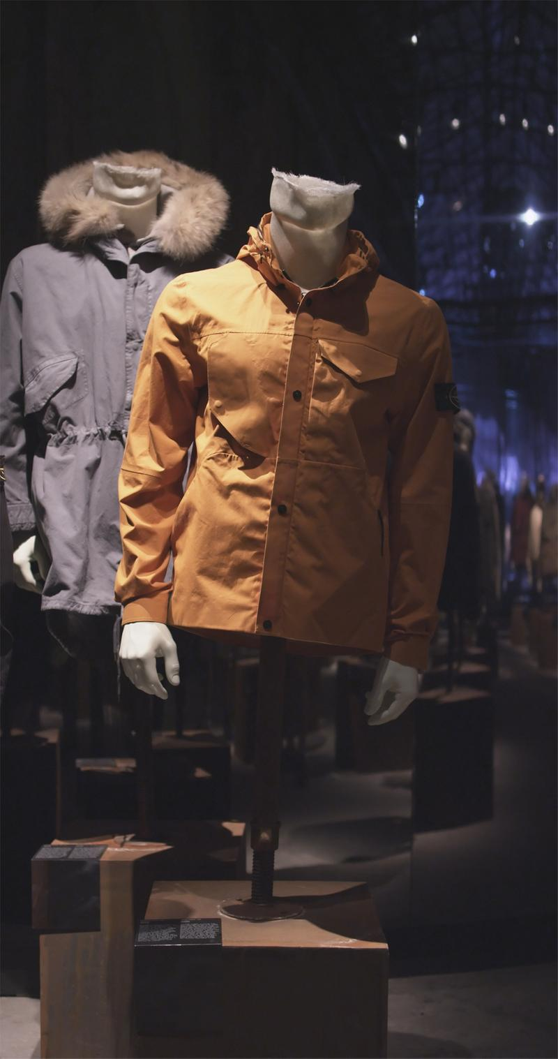 Two jackets, one dark, one orange, displayed on mannequin busts in exhibition hall