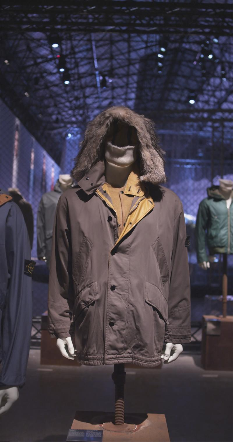 Dark colored button up jacket with fur trimmed hood, flap pockets, and yellow interior details displayed on mannequin bust in exhibition hall