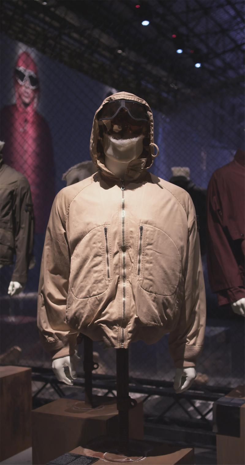 Zippered hooded tan jacket displayed on mannequin bust with zippered chest pockets