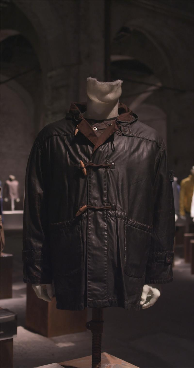 Black jacket with toggle closure and dark brown collar lining displayed on mannequin bust