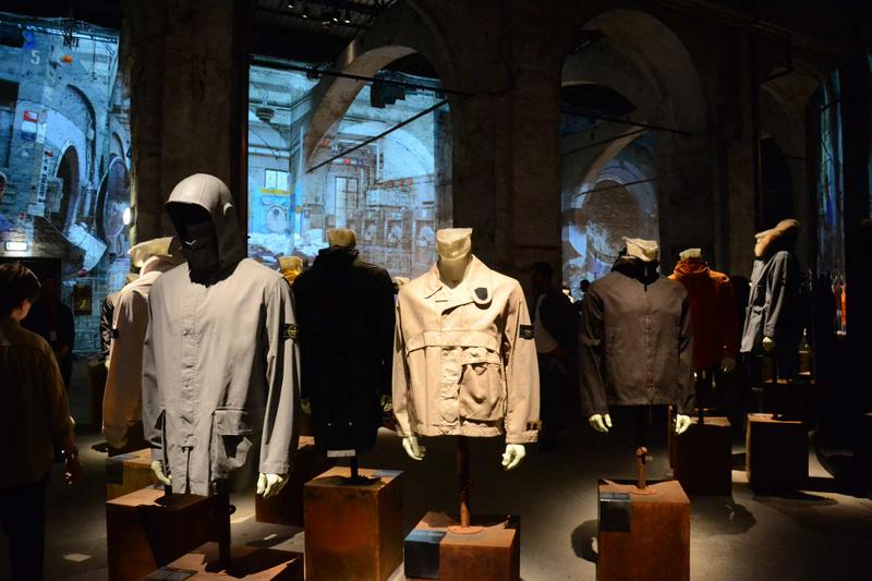 Various jackets in different styles and colors displayed on mannequin busts in front of stone archways with images projected on the walls