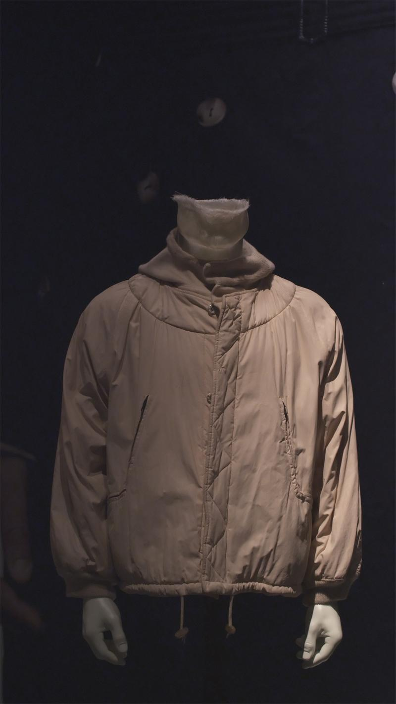 Tan jacket with drawstring waistband, zippered side pockets, and high collar displayed on mannequin bust