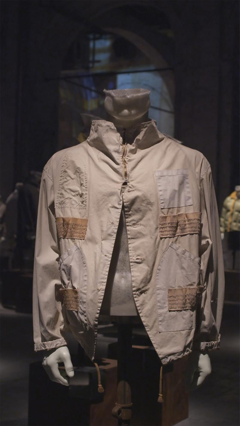 Tan jacket with darker tan panel accents, zippered collar and buttoned closure below, displayed on mannequin bust