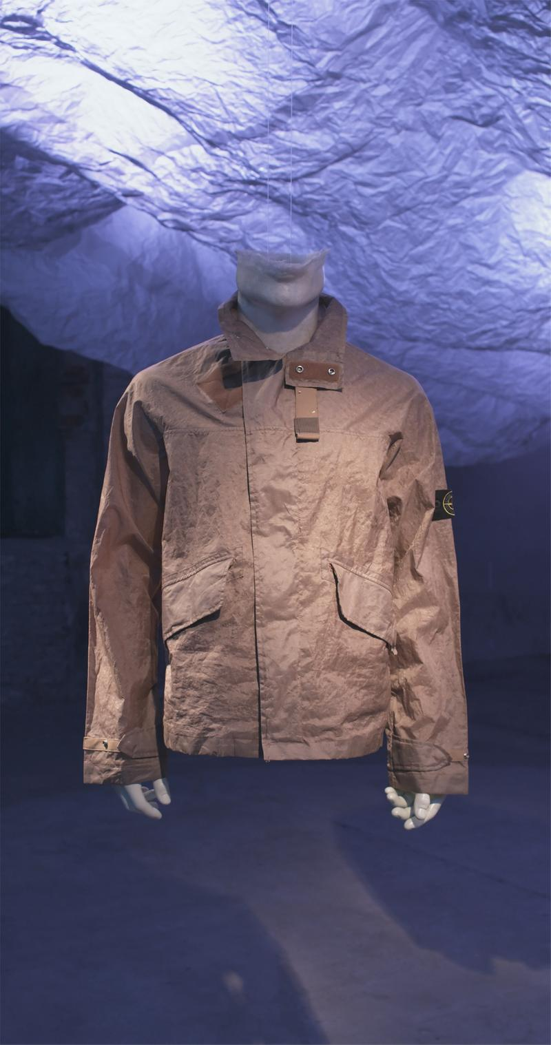 Light brown jacket with snap button collar, flap pockets, and Stone Island badge on upper left sleeve displayed on mannequin bust