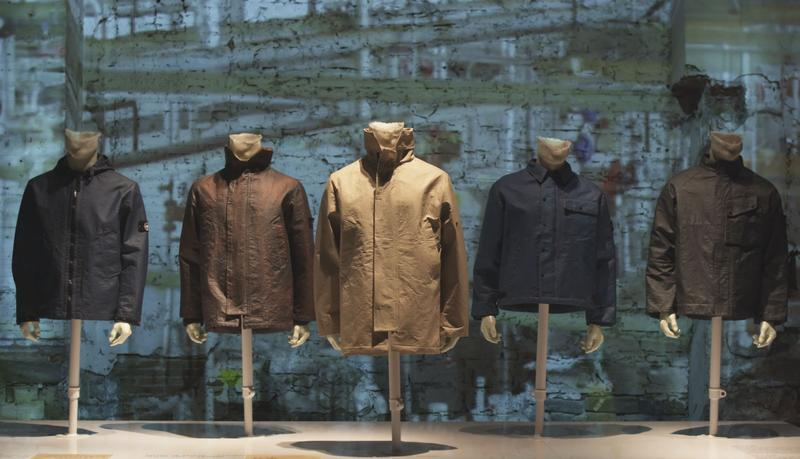 Five jackets in black, brown, camel, dark blue, and dark gray displayed on mannequin busts