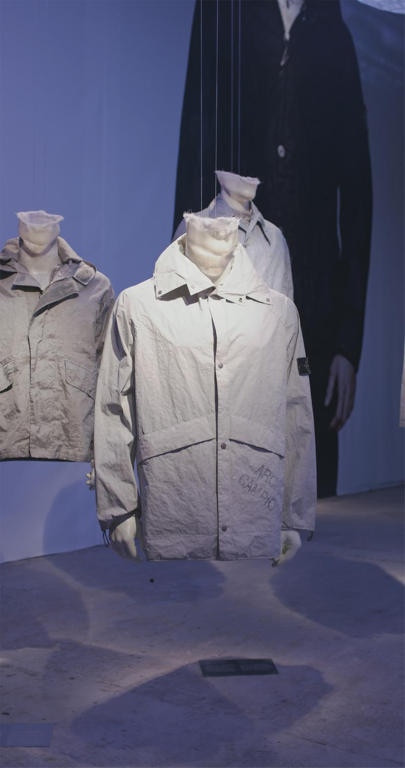 White button up jacket with flap pockets, double collar displayed on mannequin bust, with other light colored jackets in the background