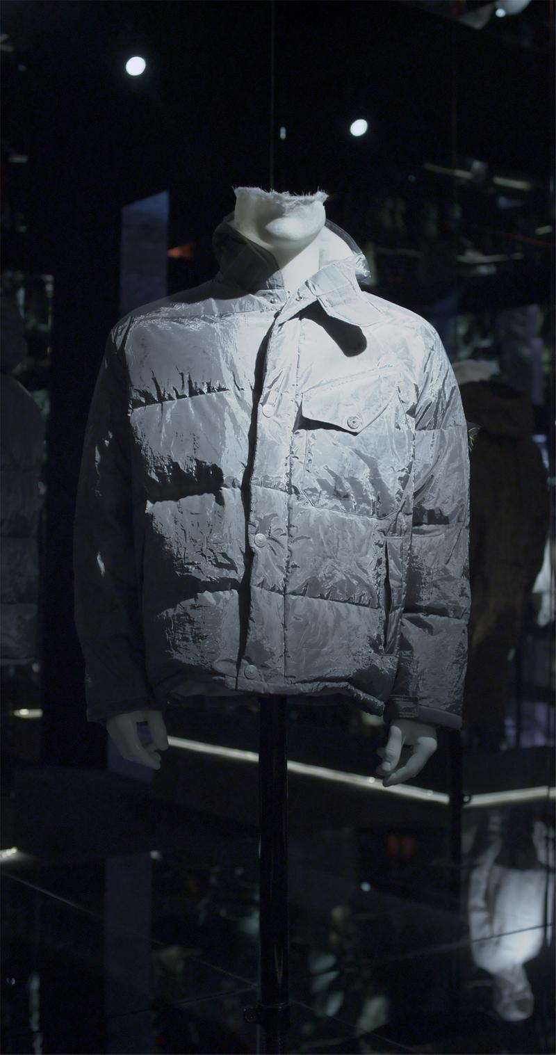 Silver puffer jacket with high collar, snap button closure and one flap pocket on left chest, displayed on mannequin bust