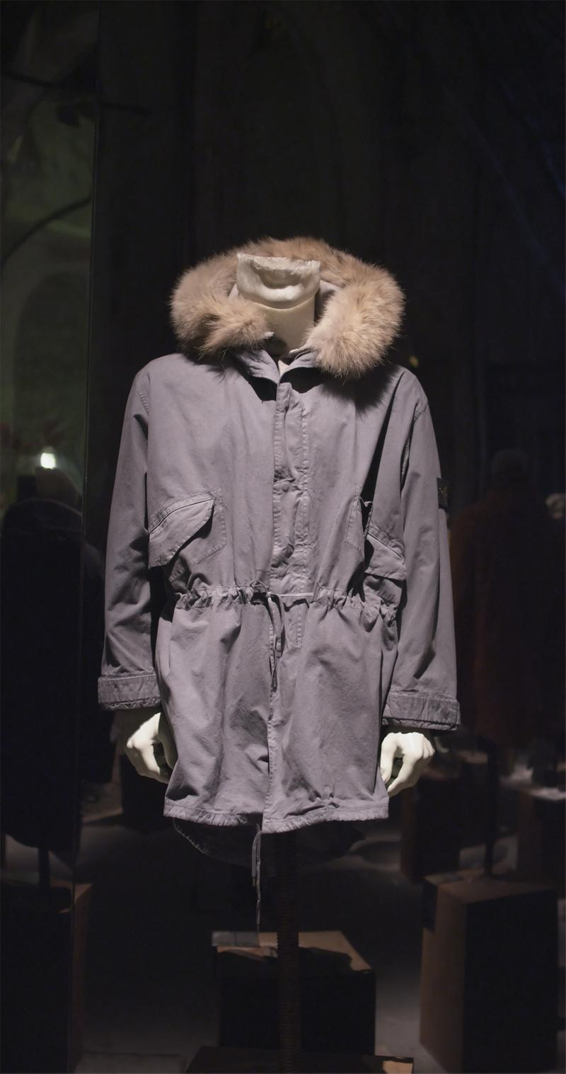 Long dark gray jacket with fur trimmed collar, drawstring waist, and flap pockets on mannequin bust