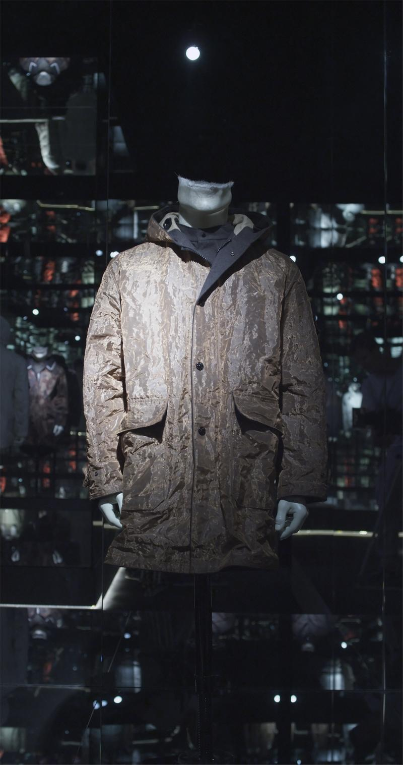 Brown hood jacket with dark lining, button closure and flap pockets, displayed on mannequin bust