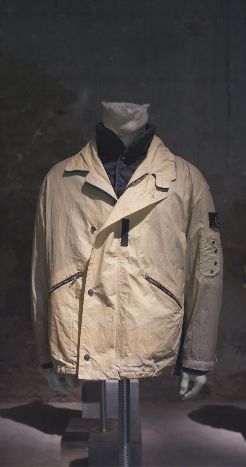 Off white jacket with button closure and notched tab collar, zipper pockets and buttoned detail on the upper left sleeve, displayed on a mannequin bust