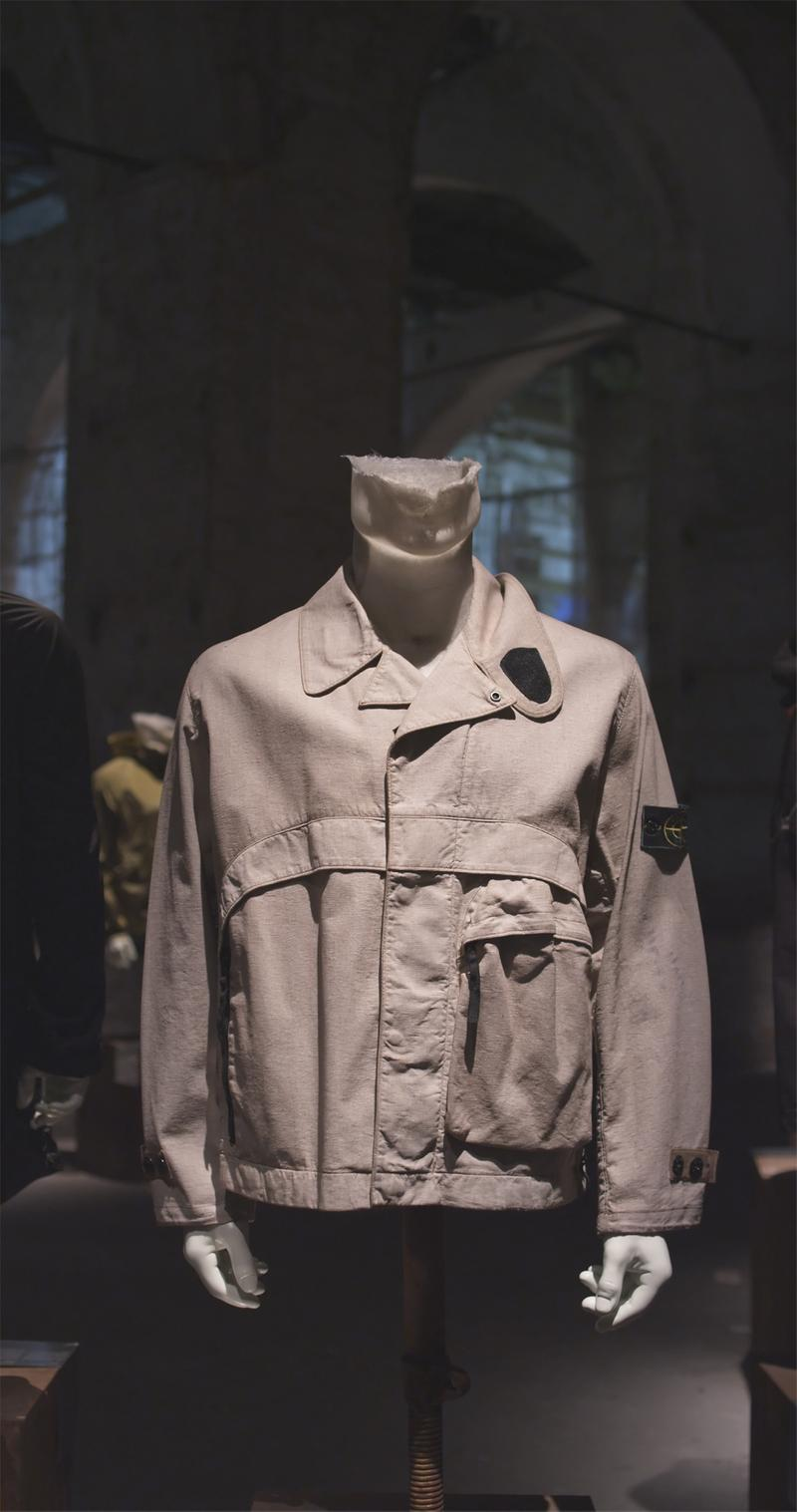Light colored jacket displayed on mannequin bust with double collar, button closure, large side pocket, and Stone Island badge on upper left sleeve