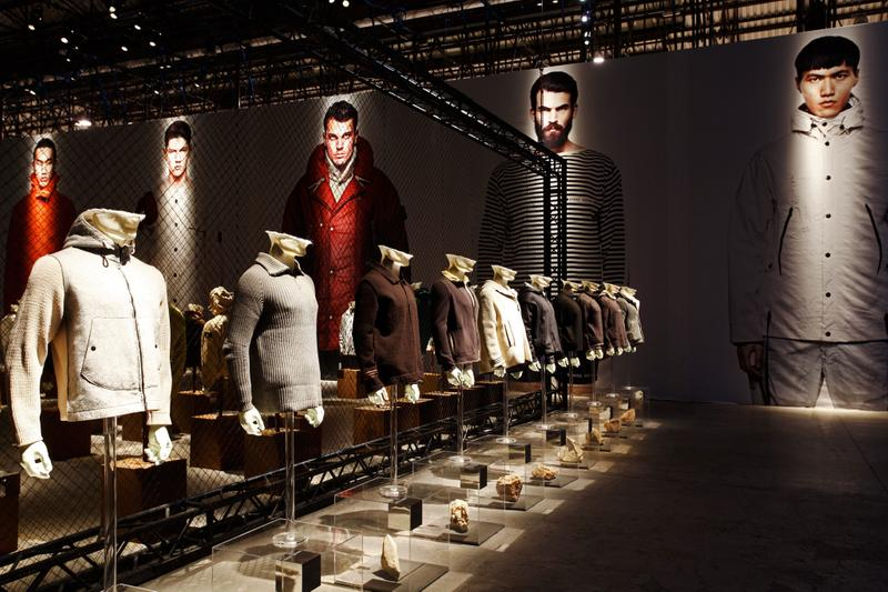 Row of various sweaters and jackets of different colors and styles displayed on mannequin busts with photo mural behind them
