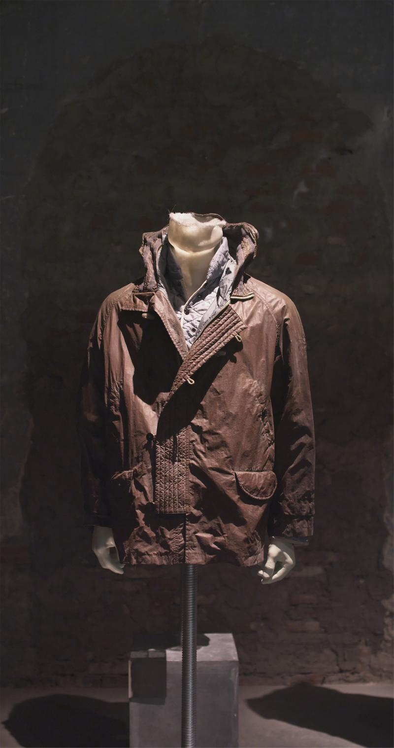 Dark brown shiny jacket with flap pockets and high collar, displayed on a mannequin bust