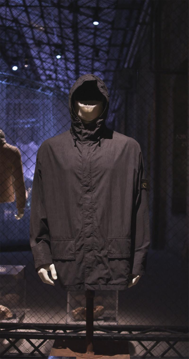 Hooded black jacket with front closure, flap pockets and Stone Island badge on left sleeve displayed on mannequin bust against chain link fence