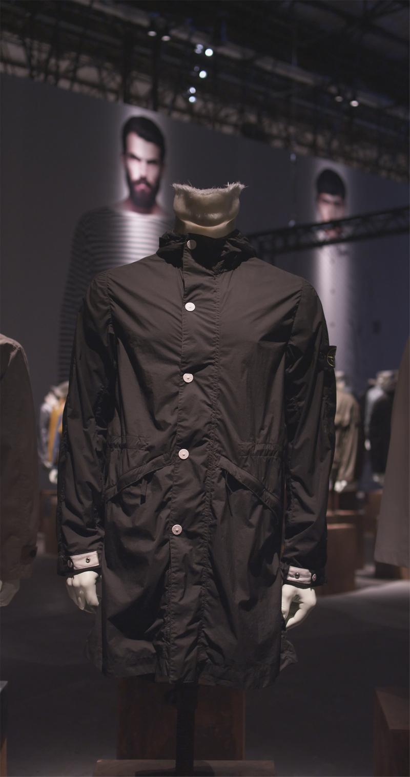 Long black jacket with white button closure and Stone Island badge on left arm displayed on mannequin bust