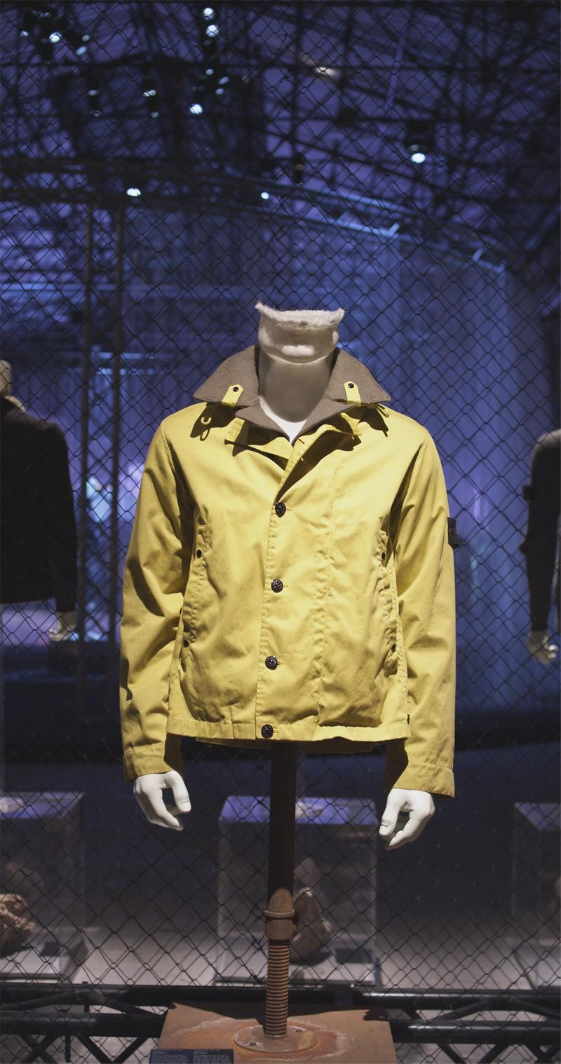 Yellow buttoned jacket with wide collar and Stone Island badge on upper left sleeve displayed on mannequin bust against chain link fence