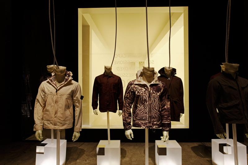 Various patterned and solid jackets displayed on mannequin busts mounted on translucent blocks