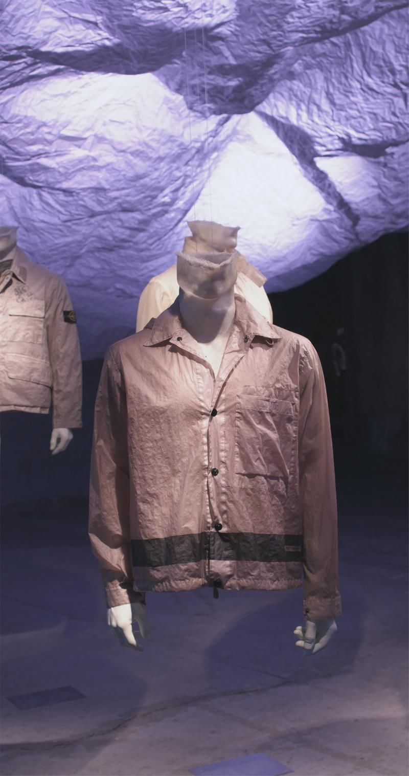 Beige button up jacket with shirt collar, button closure and contrasting band on the bottom displayed on mannequin bust