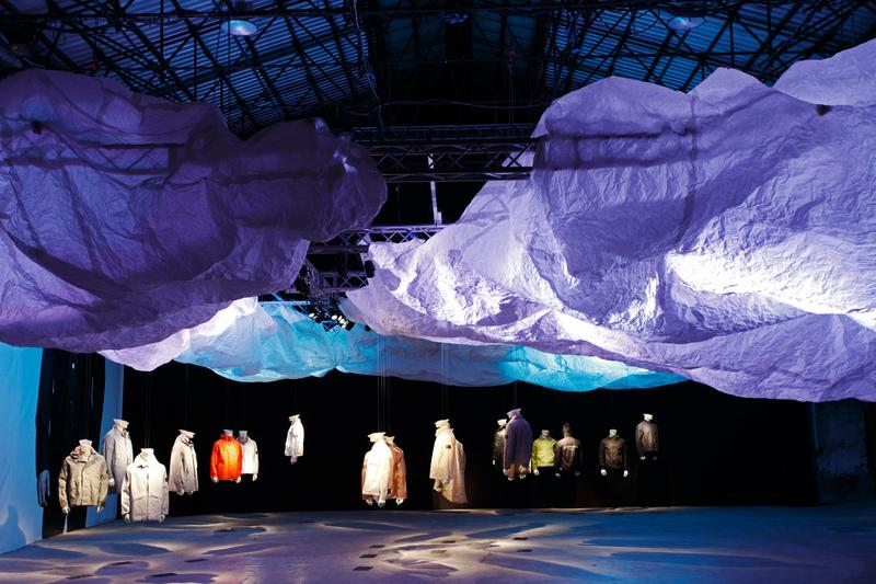 Exhibition hall with cloud structure under blue and purple lighting and jackets on display