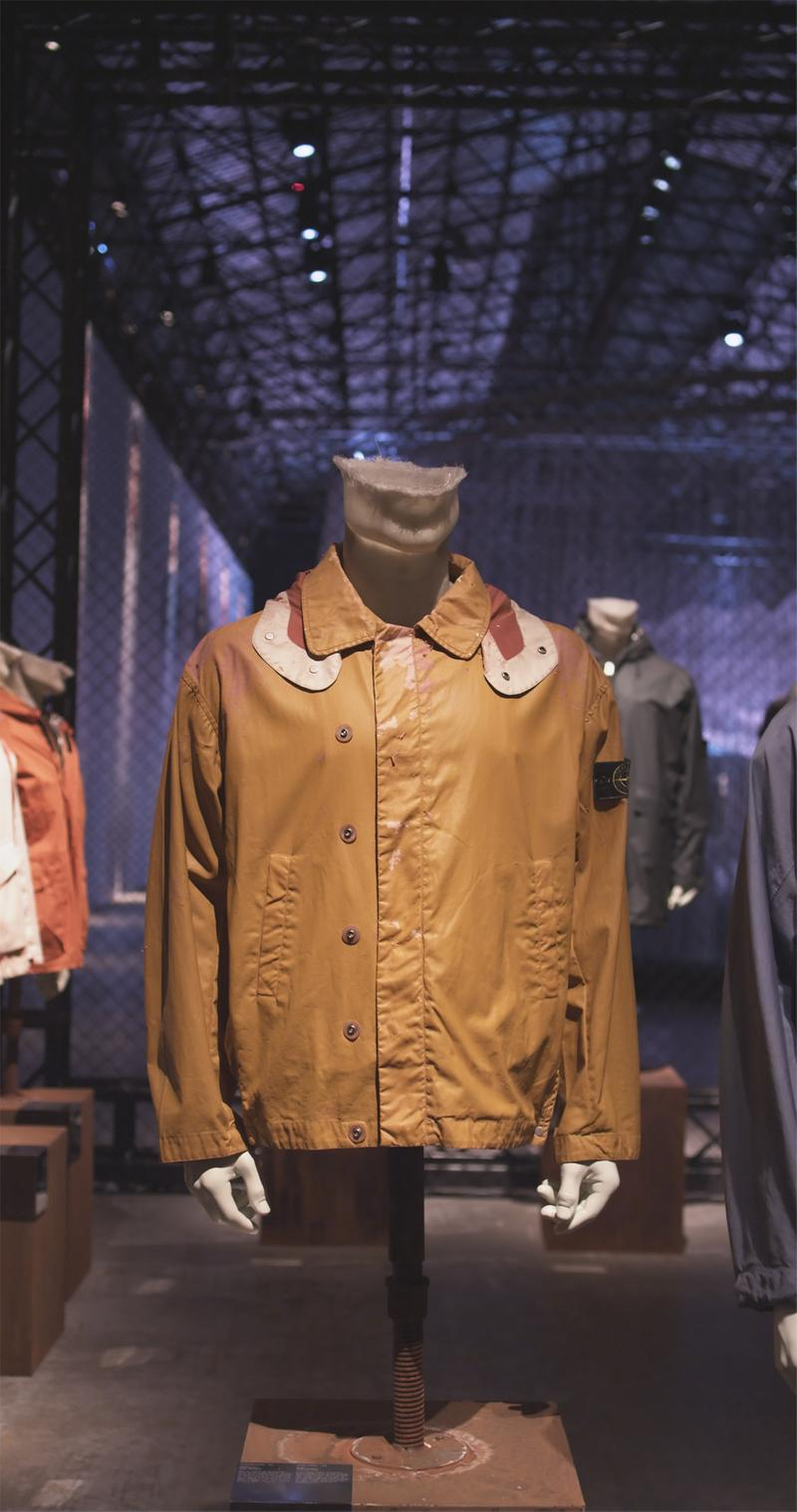 Light tan jacket with wide collar with contrasting placket displayed on mannequin bust in exhibition hall