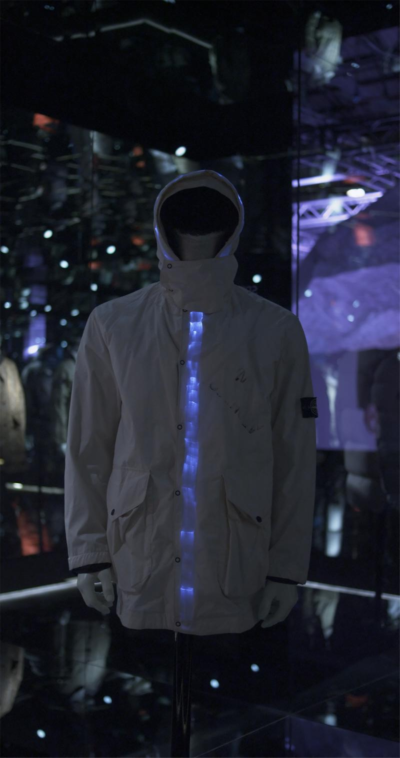 Hooded parka with blue zipper placket, flap pockets and Stone Island badge on upper left sleeve, displayed on mannequin bust
