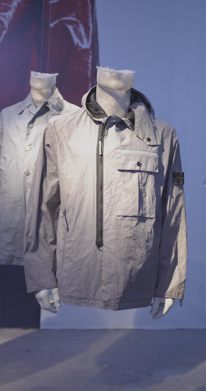 Light gray asymmetrical zip up jacket with hood, buttoned patch pocket on the chest and Stone Island badge on upper left arm, displayed on mannequin bust
