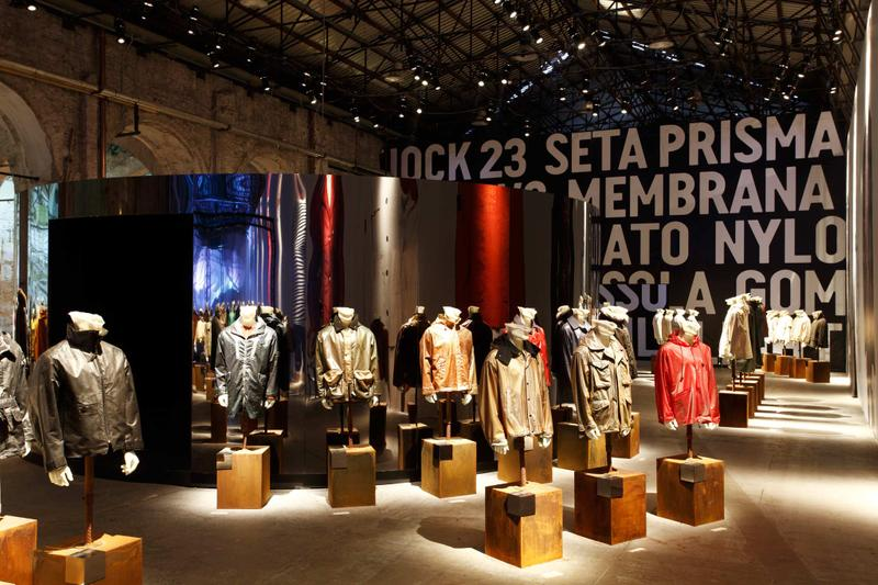 Various jackets in different styles and colors displayed on mannequin busts in exhibition hall with word mural in the background